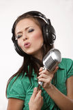 Amazing beautiful girl with studio microphone. Amazing beautiful girl with professional studio microphone and headphones on white background in studio shooting stock images