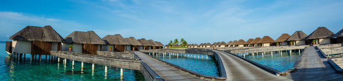 Amazing beautiful tropical beach panorama of water bungalos with bridge near the ocean at Maldives. Amazing beautiful tropical beach panorama of bungalos with Stock Photography