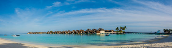 Amazing beautiful tropical beach panorama of water bungalos  near the ocean with palm trees and white sand at Maldives Royalty Free Stock Photography