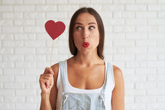 Amazing beautiful woman holding red paper heart and look at it. White brick wall on background Royalty Free Stock Photography