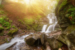 Amazing beauty of Alps mountains waterfall. Summer waterfall in Alps with soft sun rays at evening Royalty Free Stock Photography