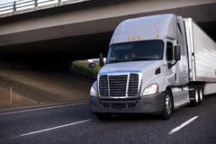 Amazing big rig grey semi truck with semi trailer driving under. Modern professional big rig grey semi truck with refrigerator semi trailer driving under bridge stock photo