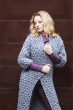 Amazing blonde girl posing in a gray knitted coat on the street on a background of rusty metal wall. fashion. beauty Stock Images