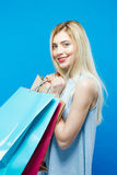 Amazing Blonde with Lond Hair and Charming Smile on Blue Background in Studio. Happy Woman Holding a Lot of Shopping Stock Image