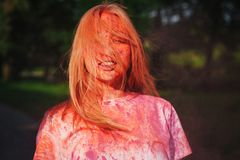 Amazing blonde model having fun with colorful orange paint at the park. Concept for festival Holi. Amazing blonde woman having fun with colorful orange paint at stock photo