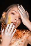 Amazing blonde model with professional makeup and gold foil on h Stock Image