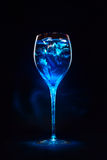 Amazing blue cocktail with ice cubes on dark background. Magic l Stock Photography