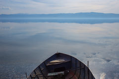 Amazing blue landscape of a metal row boat on a lake bank Royalty Free Stock Image