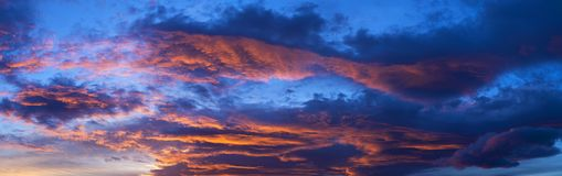 Amazing blue and orange sky at sunset. Amazing view of thick clouds floating on evening sky during sunset royalty free stock photos
