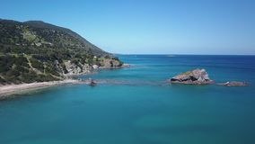Amazing blue water of warm sea near rocks of coast in sunny day, aerial view stock footage