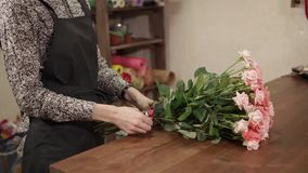 Amazing bouquet of roses on a table. Close up shot of a woman`s hands derocating a beautiful bouquet of roses. She is tying knot on it indoor stock video