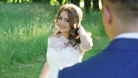 Amazing bride posing at her handsome groom, walking and kissing. Slowly stock footage