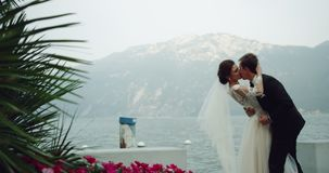 Amazing bride in white long dress kissing romantic with the groom in a beautiful place wonderful landscape in the