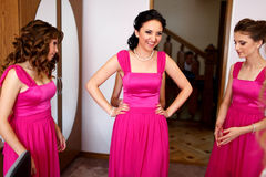 Amazing brides in pink dresses talk in a room while they wait fo Royalty Free Stock Photography