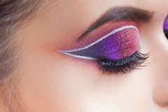 Amazing Bright eye makeup. Eye shadow with a purple tint and an unusual white arrow stock images