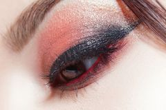 Amazing Bright eye makeup with a wide arrow. Brown and red tones, colored eyeshadow. Close up royalty free stock photo