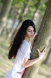 Amazing brunette lady with long curly hair, woman leaning on tree Stock Images