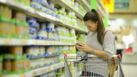Amazing Brunette Mother with Shopping Cart Buying Healthy Baby Food in the Hypermarket Standing Near Shelf With Goods. stock footage