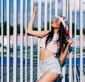 Amazing brunette woman posing in pink top, jeans shorts, baseball cap and trendy sunglasses in colors of the American flag. USA.