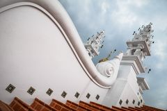 Amazing buddhist architecture with curved white wall with low angle view and beautiful cloudy sky royalty free stock images