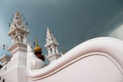 Amazing buddhist architecture with curved white wall with low angle view and beautiful cloudy sky royalty free stock image