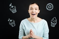 Excited middle aged woman feeling impressed while looking at the cakes. Amazing cakes. Positive hungry woman looking at the tasty cakes in a new cafe and feeling royalty free stock image