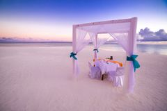 Love beach. Romantic beach dinner, white sand and white tent. Sunrise or sunset colors for couple and honeymoon background concept Stock Images