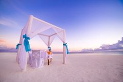 Love beach. Romantic beach dinner, white sand and white tent. Sunrise or sunset colors for couple and honeymoon background concept Royalty Free Stock Image