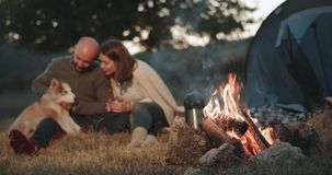Amazing capturing video of a cute couple at the picnic beside of campfire spending a romantic time together with their stock footage