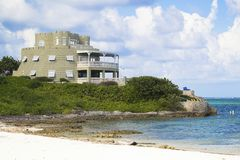 Amazing castle beach home in Grand Cayman Islands. With blue sky and clouds royalty free stock photos