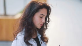 Amazing caucasian girl with brown hair in trendy white jeans coat communicating with a smartphone, wind swaying hair stock footage