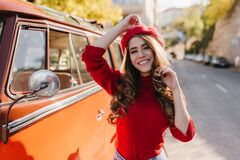Amazing caucasian girl with curly brown hair spending time outdoor in sunny october morning. Photo of romantic lady with
