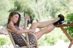 Amazing charming leggy women sitting on wooden bamboo chair Royalty Free Stock Photos