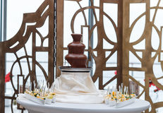 Amazing chocolate fountain. Beautiful restaurant interior table decoration for wedding, chocolate fountain royalty free stock photography