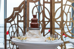Amazing chocolate fountain. Beautiful restaurant interior table decoration for wedding, chocolate fountain royalty free stock photos