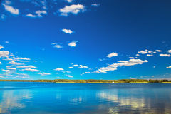 Amazing clear lake under blue sunny sky. Green forest coast in the background Stock Photos