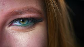 Amazing close up eye of caucasian blonde woman in green glowing eyeshadows and perfect cosmetics, looking at camera. Relaxed and not blinking, in dark studio stock footage