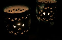 Amazing close up of lit candles in a beautiful blue candle holder stock photo