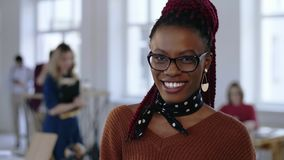 Amazing close-up portrait of young African creative business woman in eyeglasses with white teeth smiling at office. stock video footage