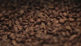 Amazing close up view of a big heap of fragrant brown coffee beans in a mixing roasting machine. Coffee making. No stock video