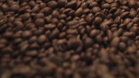 Amazing close up view of roasted coffee beans in a process of mixing. Great close up view of traditional coffee roaster stock footage
