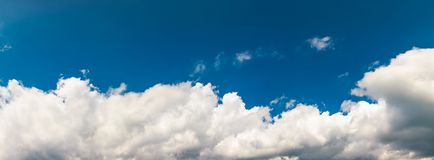 Amazing cloud formations on a blue sky. Amazing cloud formations on a dark blue sky. beautiful side lit cloudscape panorama in summer Royalty Free Stock Photography