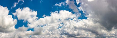 Amazing cloud formations on a blue sky. Amazing cloud formations on a dark blue sky. beautiful side lit cloudscape panorama in summer Royalty Free Stock Photos