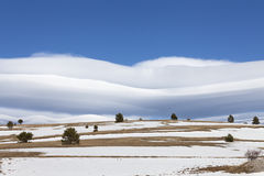 Amazing clouds on blue sky and desert snowy hill. Stock Photography