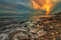 Amazing clouds like flame in the sky. Amazing clouds like fire in the sky over the sea coastline stock image