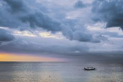 Amazing cloudy sunset sky with boat in Bali. Amazing cloudy sunset sky above the sea with boat in Bali royalty free stock photos