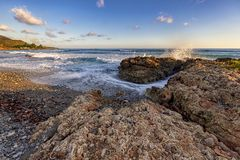Splash of seawater at rocks on the shore. Sea waves over the rocks. Amazing coast view near Santiago de Cuba. Splash of seawater at rocks on the shore. Sea waves royalty free stock images