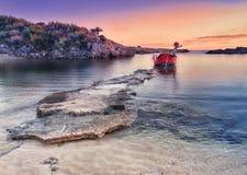 Amazing coastal landscape at sunset. Rock beach and single littl. E boat stock photos