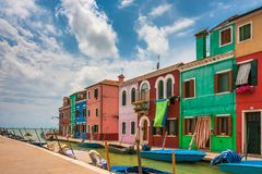 Amazing colorful architecture on narrow Burano canals. Typical vibrant Burano houses with striped curtains on front door on a summer day, Italy Stock Photos