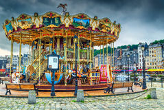 Amazing colorful French Carousel in Honfleur, Normandy, France, Europe. Spectacular retro carousel in the city. Merry-go-round with horses and landau in the Stock Images